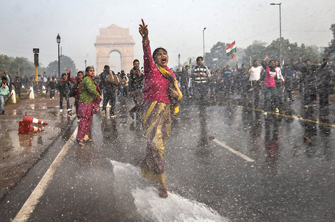 Women facing the Police's water cannons in Delhi